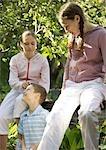 Deux filles, assis au sommet de la rampe et un garçon, appuyé contre la rambarde