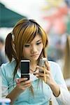 Adolescente à l'aide de deux téléphones cellulaires