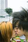 Teenage couple kissing in urban setting