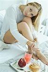 Woman having breakfast in bed, looking at camera