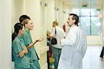 Junge Krankenhauspersonal im Chat mit Reifen männlichen Arzt, Seitenansicht