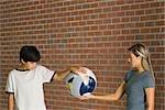 Boy and woman holding bandaged globe together