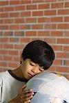 Boy leaning face against bandaged globe