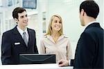 Customer service representatives smiling at businessman waiting at counter