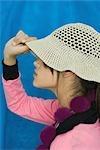 Adolescente en tirant le chapeau de soleil sur les yeux, vue latérale, portrait