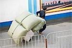 Homme karting coussins à travers la rue, la Chine, Province du Guangdong, Guangzhou.