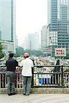 Chine, Province du Guangdong, Guangzhou, deux hommes à la recherche sur le site de construction, vue arrière