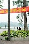 Chine, Province du Guangdong, Guangzhou, couple assis sur un banc près de l'eau, en regardant la vue, vue arrière