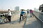 Chine, Province du Guangdong, Guangzhou, cyclistes traversant le pont