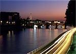France, Paris, voitures voyageant sur le quai à côté de la rivière Seine dans la nuit, floue.