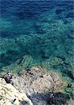 France, Corsica, people fishing on rocks, high angle view