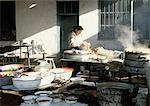 China, Xinjiang Province, Turpan, woman preparing steamed buns in outdoor kitchen