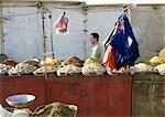 China, Xinjiang, Turpan, man behind stall in open air market