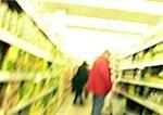Personnes debout dans l'allée au supermarché, floue