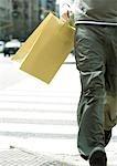 Junger Mann mit Einkaufstasche Wandern