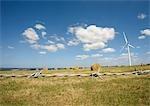 Éolienne en champ avec balles de foin, fil de fer barbelé au premier plan