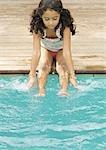 Mädchen sitzen am Rand des Pools mit Händen und Füßen im Wasser