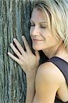 Femme s'appuyant sur le tronc de l'arbre, les yeux fermés, souriant, recadrée vue, plein cadre