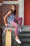 Woman Sitting on Steps With Skateboard, Portland, Oregon, USA