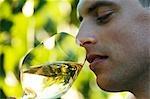 Young man tasting white wine in vineyard