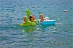 sisters chatting on floaties in lake