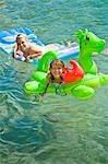 sisters on floaties in lake