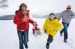 Parents et son frère tirant Girl en traîneau en hiver