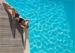 Vue surélevée d'une femme se faire bronzer au bord de la piscine