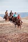 Gruppe von Cowgirls und Cowboys auf Pferden durch die Badlands, Wyoming, USA