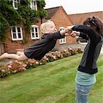 Woman swinging child outdoors