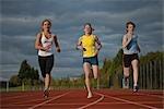 3 female athletes racing towards camera