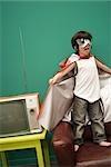 Boy in superhero costume standing on sofa