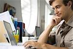 Mid-adult man using laptop computer