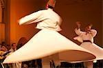 Maroc, Fes. Derviches tourneurs deux effectuent lors d'un concert à la Fes Festival de musiques sacrées du monde. Les membres de l'Al Kindi Ensemble effectuer la musique.