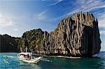Philippines,Palawan Province,El Nido,Bacuit Bay. Miniloc Island - catamaran for island hopping in Small Lagoon with unusual jagged limestone rock formations.