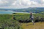 UK,Wales,Pembrokeshire. A boy runs along the Pembrokeshire Coastal Path on Dinas Head with views of Newport Bay beyond .