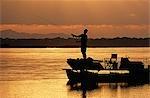 Zambia,Lower Zambezi National Park. Fly fishing for Tiger fish from a barge on the Zambezi River at dawn.