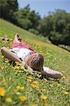 Woman Lying in a Field of Yellow Wildflowers, Near Santa Cruz, California, USA