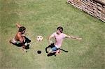 Men playing soccer on grass