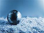 Metal globe on shredded paper