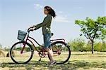 Jeune femme marchant avec vélo dans le parc