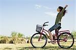 Jeune femme assise sur la bicyclette avec les bras tendus et les yeux fermés