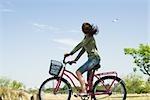 Vélo de femme, regardant le vol d'avion dans le ciel