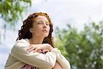 Junge Frau sitzt im Freien mit Augen geschlossen
