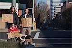 Famille détenant des signes sur coin de rue