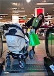 Mother Struggling with Stroller on Escalator