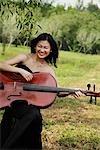 Frau spielt Cello wie eine Gitarre und lachend