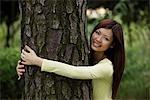 Femme chinoise s'enlaçant un arbre et souriant