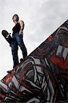 Young man standing on graffiti wall holding skateboard