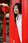 Jeune femme regardant derrière les piliers rouges